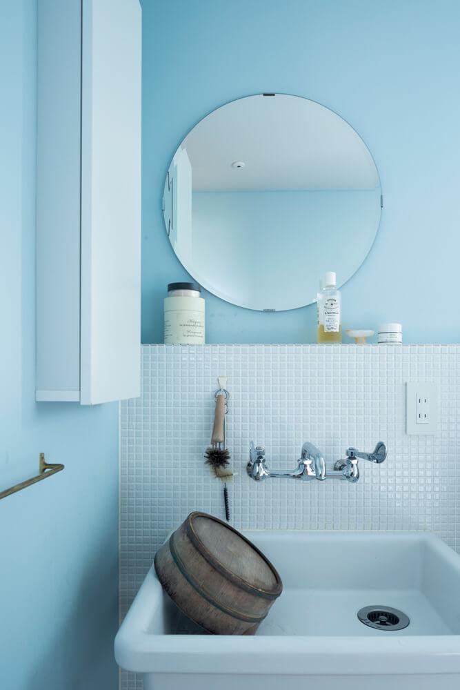 レトロ感のあるシンクとタイル、淡いブルーの壁、壁掛けの丸ミラー。装飾を排した洗面ルームにセンスが光る