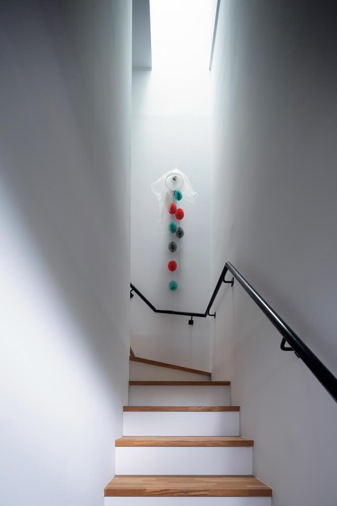 トップライトから柔らかな光が降り注ぐ。この階段が仕事モードとプライベートモードの気持ちの切り替えを行うアプローチに