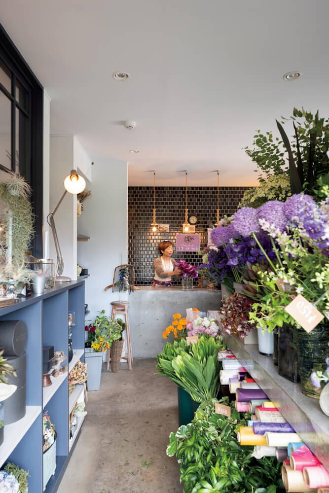 店舗スペースは、コンクリートやタイルなどで仕上げたシンプルな内装が花をいっそう引き立てる。レジカウンターと作業台もコンクリートで設え、空間に統一感を持たせた