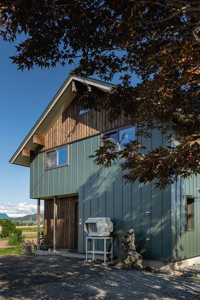 「風景に溶け込むようなみどりの家にしたい」という希望を叶えた、深い緑色のガルバリウム鋼板とカラマツを組み合わせた外観
