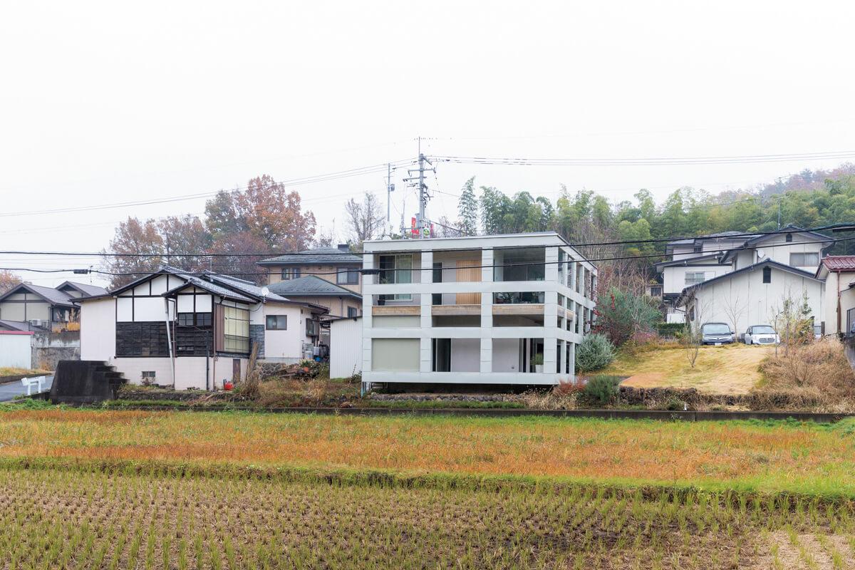 田んぼと竹林が広がる古い集落の一角にあるHさん宅。西側からは、総2階建てのように見える