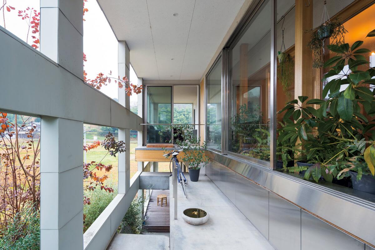 高低差約2.5mの2階と1階は、屋外と屋内それぞれに設けた階段で行き来できる設計。外部につくった屋根付きのコンクリート土間やテラスは、天候や泥汚れ、水で濡れることなどを気にせずに植物の世話ができて便利だという。ここに生まれ育ち、建築にあたって眺望を重視したHさんにとって、目線の高さによって景色の見え方が変化するのもこの地形ならではの楽しみ。