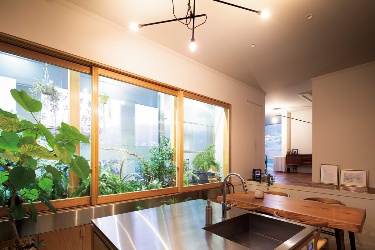 スキップフロアを取り入れたLDK。流し付きの四角い大きなアイランドキッチンはステンレス製の天板で、買ってきた食料品などをすぐに広げられ、植物の水やりにも便利。植栽空間は窓を閉めるとショーケースのよう