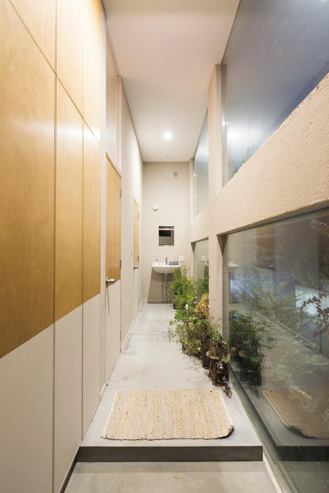 トイレへの通路を兼ねた玄関ホール。新築時は道路から丸見えだったが、植栽が育ったことで明るくほっとできるスペースに