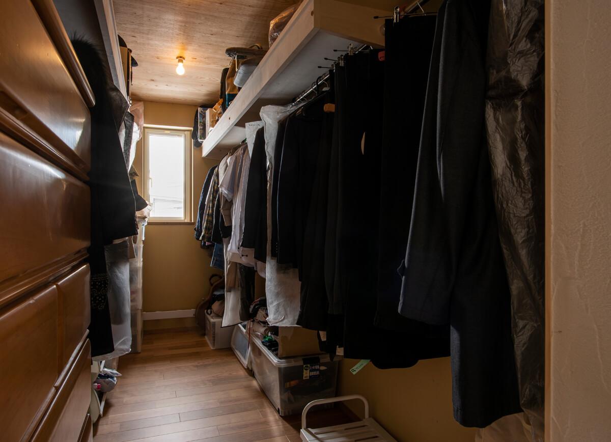 旧宅で使っていたタンスが収まる寸法でウォークインクローゼットを設計。使用頻度の低い服にはカバーをかけて