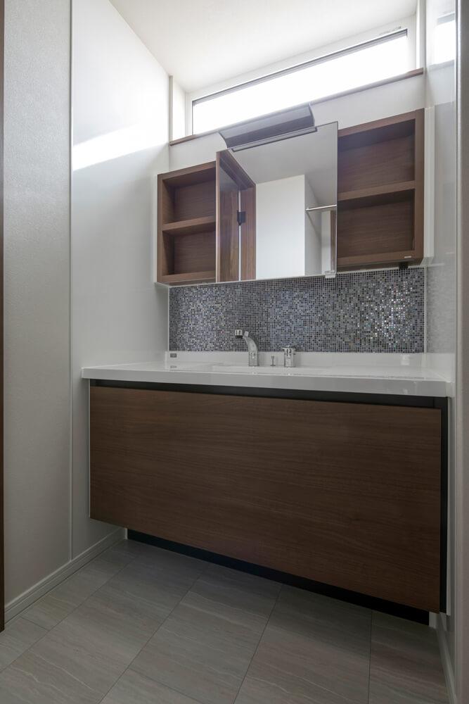 お気に入りの家具のように設置されたワイドサイズのシステム洗面台。上部の明かり採りの窓から入る自然光で明るく清潔な洗面空間