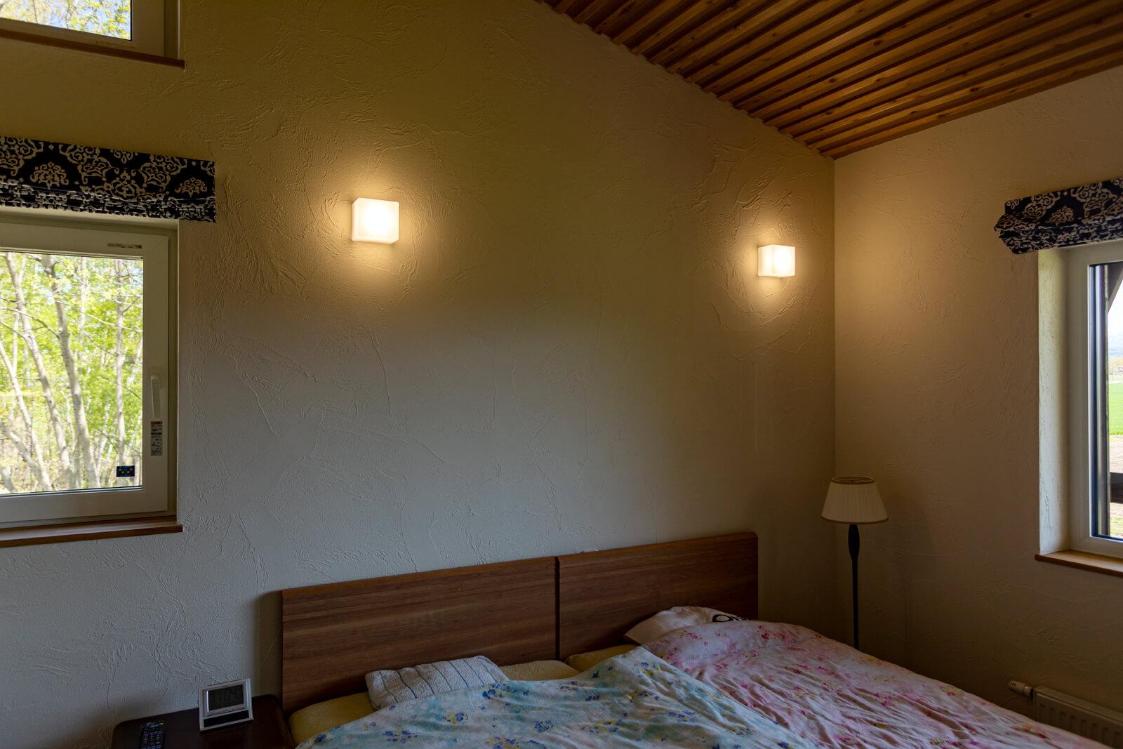 周囲の森や山並みを望む開口が設けられた2階主寝室。「冬は暖かく、目覚めたらすぐに布団から出られます」(奥さん)