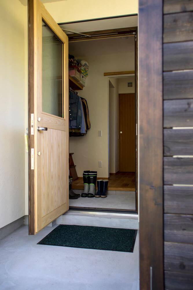 「広い庭で思う存分庭づくりを楽しみたい」という奥さんの希望で設けられた専用の裏玄関。土汚れが付いた衣類をすぐに洗えるよう、洗濯機も完備