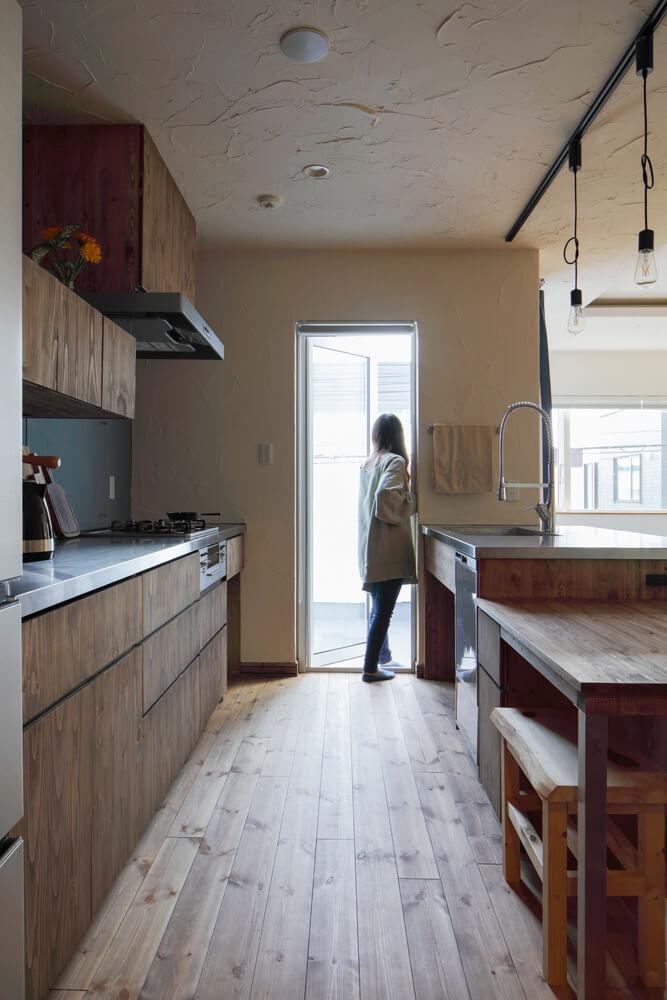 キッチンからバルコニーへの動線。無垢のパイン材の床が美しくまっすぐと伸びる