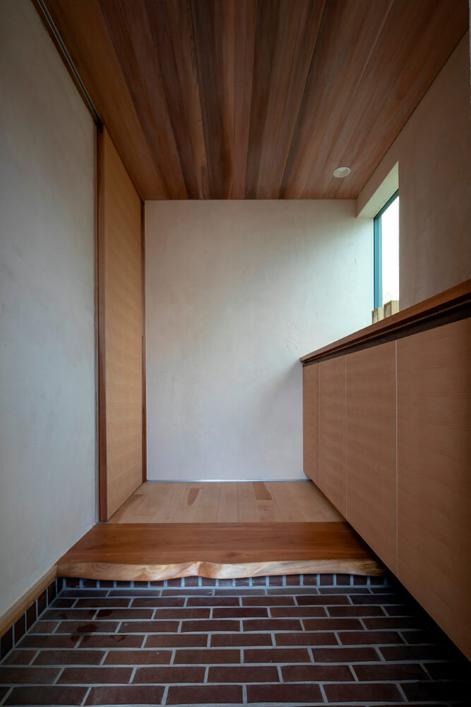 上がり框に耳つきの無垢材を使用した玄関。床は江別のレンガを使用した