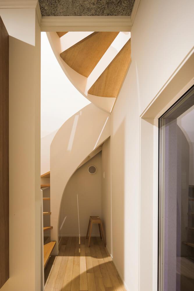 緩やかに弧を描く回り階段。直線的なデザインのなかに有機的なラインを用いることで、空間の緊張感を和らげる