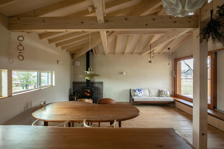 キッチンからリビングを見る。ダイニングテーブルは、当別町の家具工房 「旅する木」によるオリジナル。来客時は薪ストーブでピザを焼いて振舞うこともあるそう。「暖かさはもちろんのこと、炎を眺めてくつろいだり、料理をしたりと、薪ストーブには楽しみ方がたくさんありますよね」