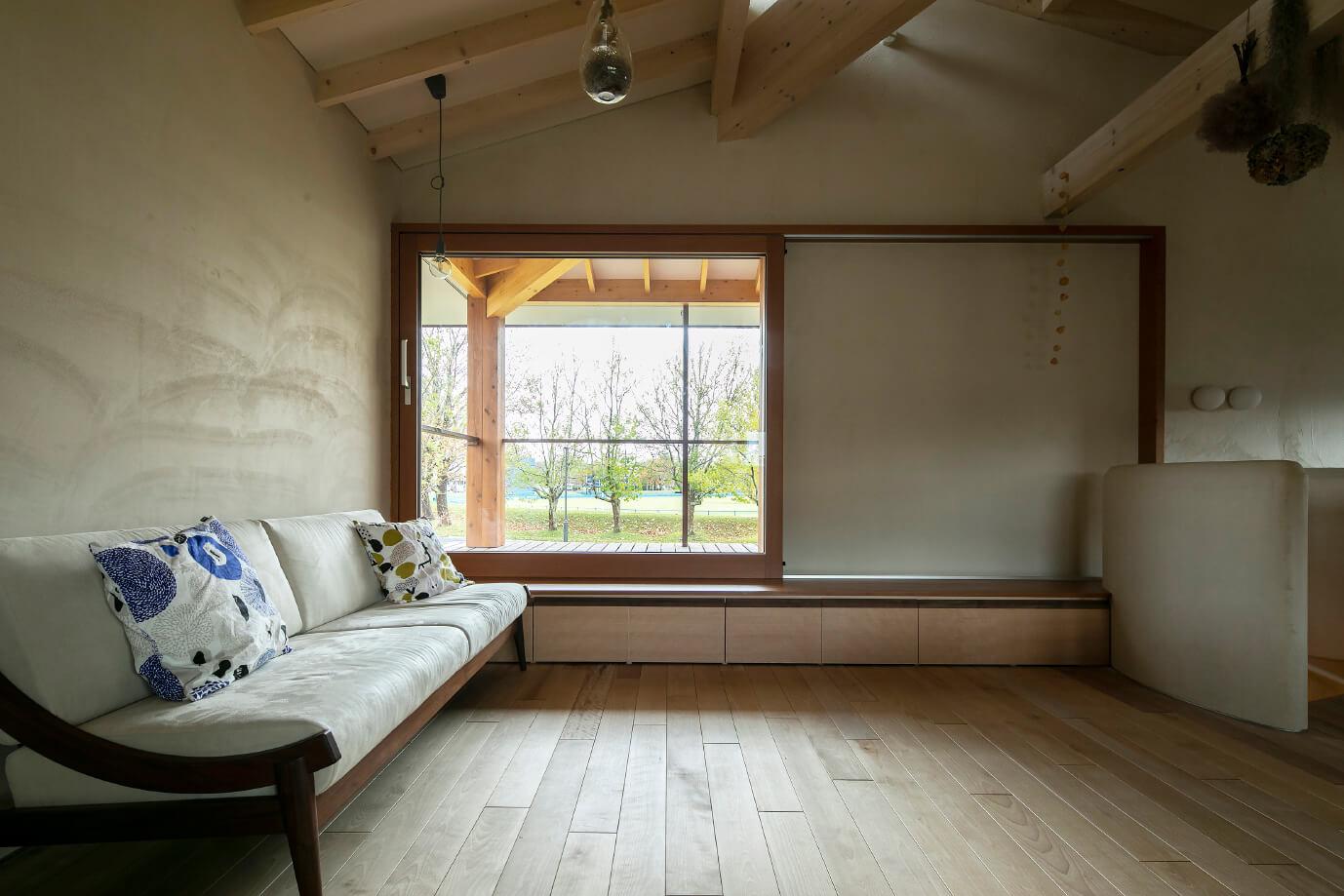 緑豊かな公園が広がるリビングの窓の向こうにはウッドデッキがある。2階のソファも1階同様「moonlit-studio(ムーンリットスタジオ)」のもの