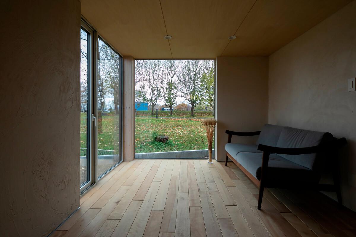 ソファは江別のオリジナル家具工房「moonlit-studio(ムーンリットスタジオ)」のもの。大きな開口が、緑豊かな外のつながりを演出