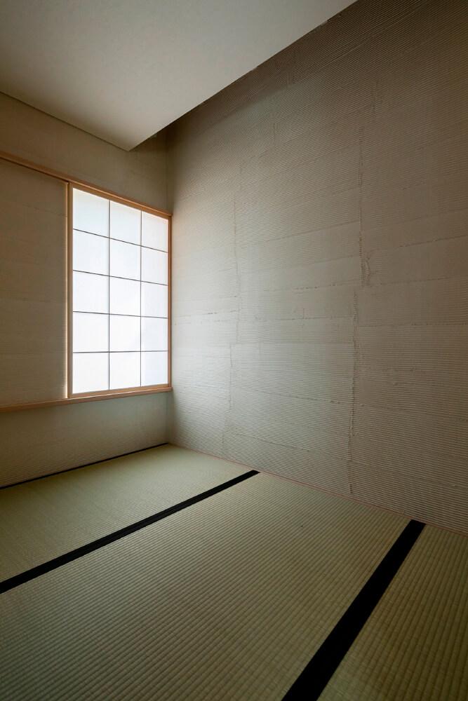 客間としての利用を想定してつくられた和室。くし引き仕上げの稚内珪藻岩の塗り壁がアクセントに