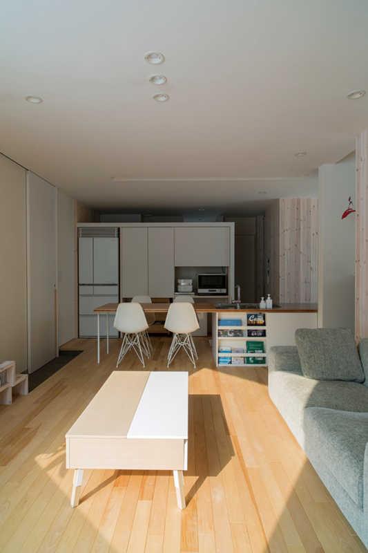 リビングの南東からキッチン方向を見る。キッチンとダイニングが一体となったミニマムな設えが、空間を広々と感じさせることに一役買っている。正面の収納奥の空間は、子世帯用の水まわりスペース