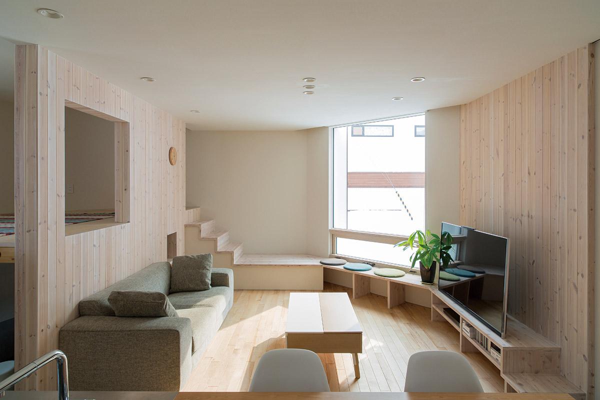キッチンからリビングを眺める。南窓からの光が木質の内装材に柔らかく映り、夏は美しく外の景色を切り取る