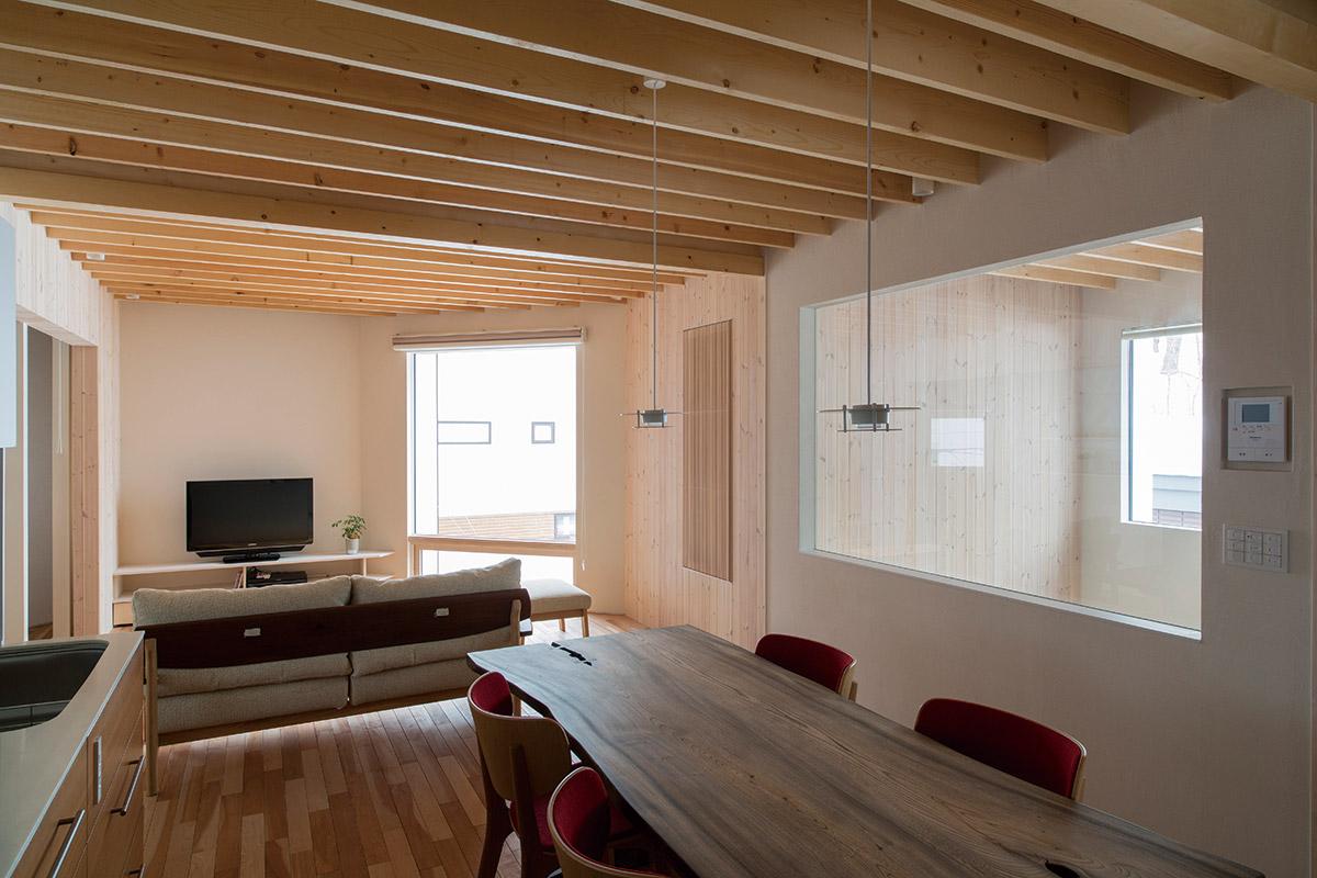 2階親世帯のダイニングからリビング方向の眺め。天井は梁を現しにして、無垢材の床とともに木質感のある内装。右手は1階へつながる階段の吹き抜けで、採光と温熱環境に配慮してFIX窓としている
