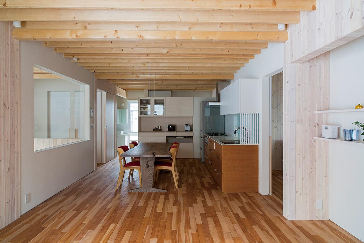 リビングからダイニング・キッチン方面を見る。ランダムに張られた床材がデザインのアクセントになっている。右手は寝室などのプライベートゾーン、奥に水まわりスペースが配置されている