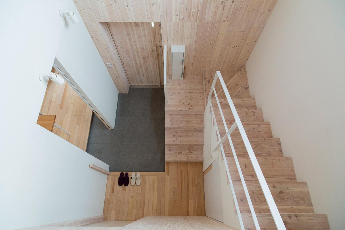 2階の階段の踊り場から1階の玄関方向を見下ろす。目地が合った内装材の縦ラインが美しい。写真手前の壁の奥は、ヒートポンプ機器置き場を兼ねた収納スペース、階段下は下駄箱となっている