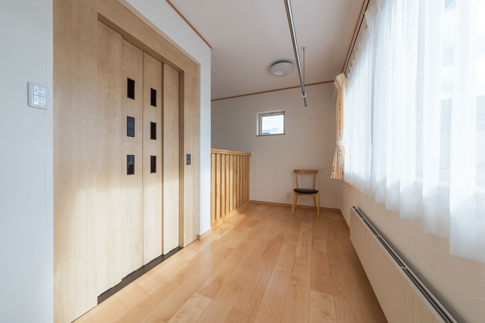 洗濯物干しなど多目的に使える3階ホールとホームエレベーター。奥は2階と繋がる吹き抜け