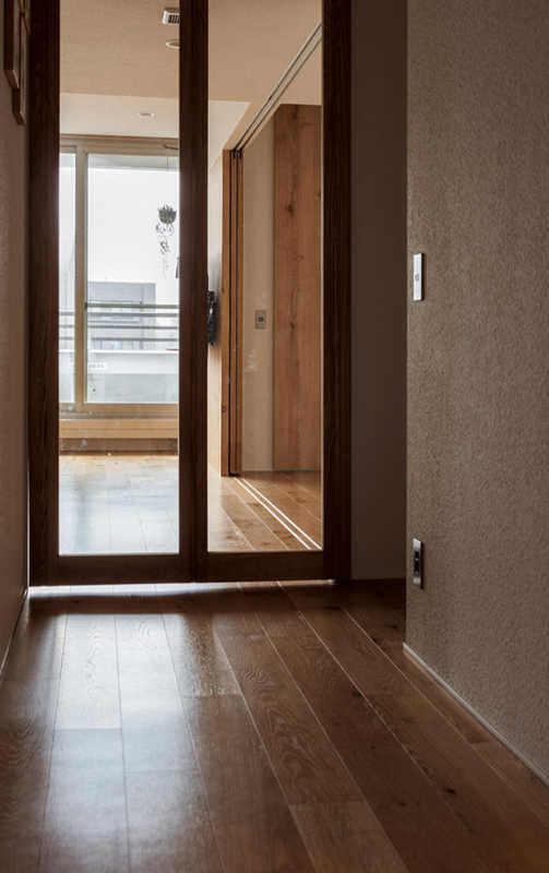 LDKへの扉はガラス製の大きな木製ドア。高層階のため、分解した状態でエレベーターに搬入し、組み立てた