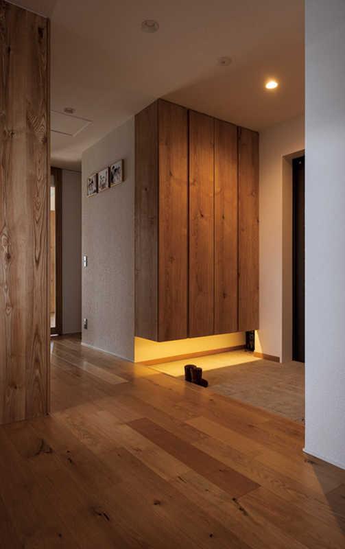 もともと広めだったという玄関スペース。大容量の木の玄関収納は床から上げた壁付けのため、下の空間も有効に活用できる