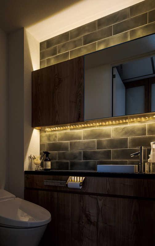 グレーのタイルと、間接照明が洗練された雰囲気をもたらす、こだわりのトイレ