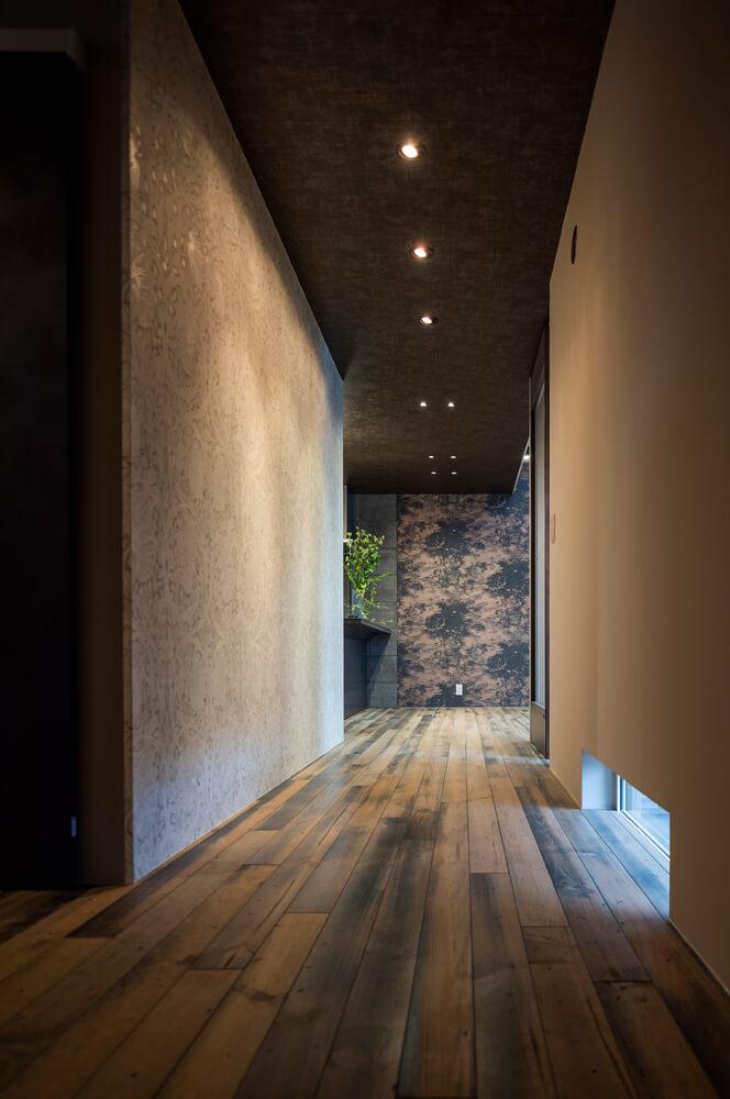 玄関からまっすぐにLDKへと伸びる廊下の左側の壁一面を、ウィリアム・モリスがデザインした「ピンパーネル」の壁紙で仕上げた