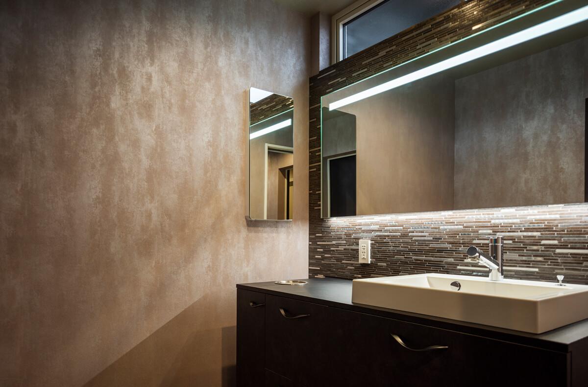 ユーティリティの壁は、ミネラル成分を含む塗り壁で仕上げた。間接照明の光で浮かび上がるテクスチャーが、空間に奥行きを感じさせる。ミラーの背面は、横長のモザイクタイルを全面にあしらった