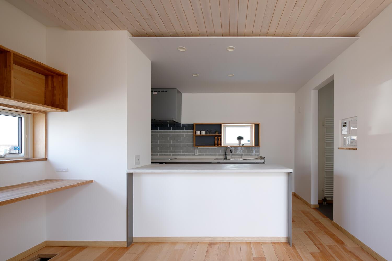 窓に面したワークスペースがあるダイニング側から見たキッチン。右奥がユーティリティへつながる。天井のスリットの段差を利用し、間接照明を設置してある