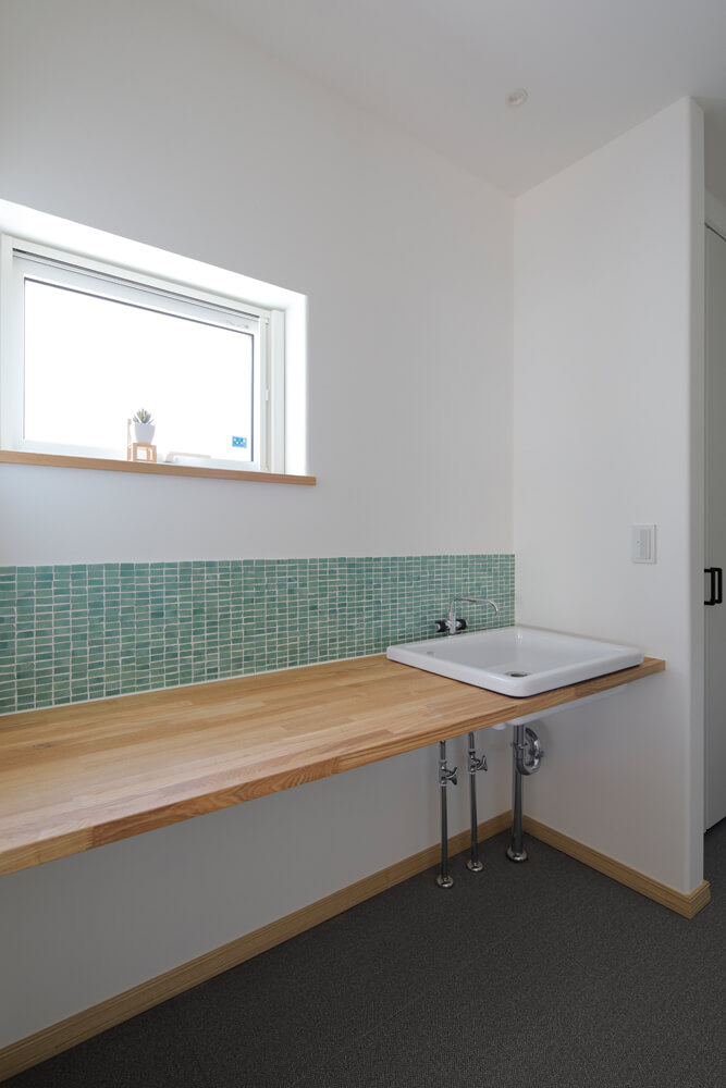 開放的で自由度のあるモザイクタイルがアクセントの洗面台。床は手入れのしやすいフロアタイルにした
