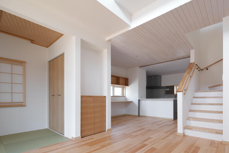 リビングの天井は無垢材の羽目板張りで、シックハウスの原因でもある揮発性有機化合物(VOC)を不使用。段差の部分に美しくはめ込まれた断面が見える。リビング奥にはコンパクトな和室をしつらえた