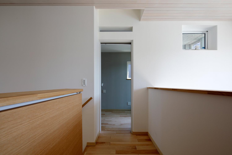 冷えた空気が階段からリビングへ降りていくのを防ぐ扉式の建具が設置された階段。主寝室入り口の天井の部分にはグリルが設置され、湿度で開口する仕組み。汚れた空気などが屋根排気塔から排出される