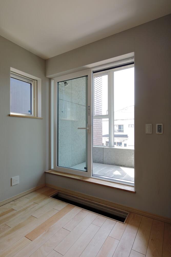 主寝室とつながるサンルームは、冬場の外気を予熱する空間。夏場は屋外物干しとして使える