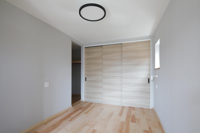 主寝室のウォークインクローゼットと壁面の収納。オガファーザーの紙クロスに薄いグレーのデュプロン塗装を施している