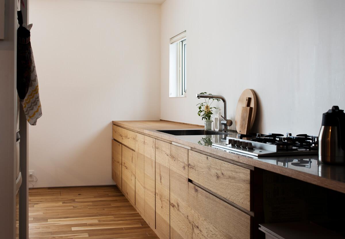ナラ材の造作キッチン。カウンター下は収納スペースで食器や調理器具がすっきりと収まる