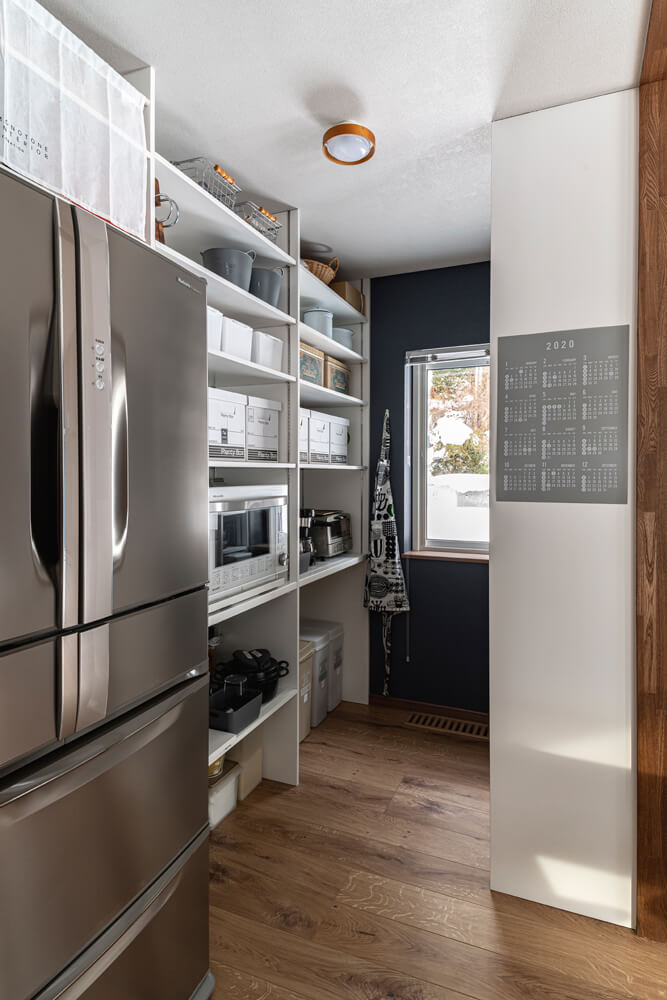 造作したすりガラス入りの引き戸の奥にはパントリー。壁に造りつけた棚には調理家電や食品のストック、分別ゴミ箱などが整然と置かれている