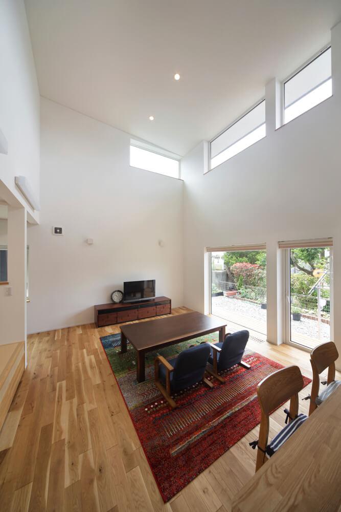 吹き抜けの高窓から採り込んだ光が室内を明るく照らす。窓が切り取る空模様をキッチンから眺めるのが奥さんのお気に入り