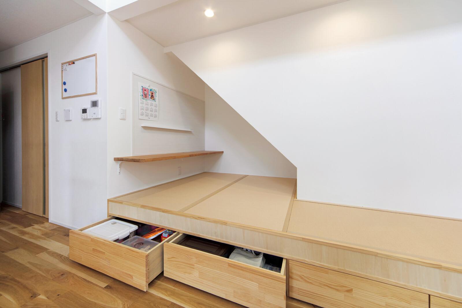 リビング階段の下に小上りの畳コーナーを設け、床下に収納を造りつけた。マグネットボードはプリントやメモ類を貼るのに便利