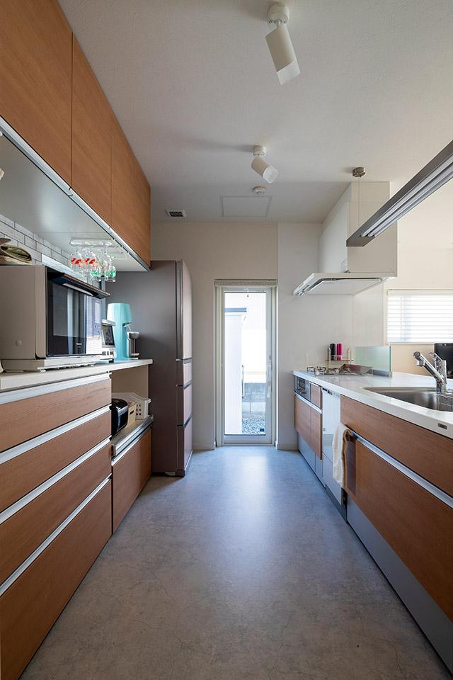通路の幅が広くて使いやすいキッチン。勝手口のすぐ外に物置を設置し、物の出し入れがラクにできる