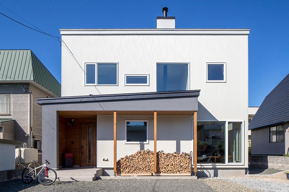 青空に白が映えるすっきりとしたフォルムの外観。玄関部分は軒先を伸ばして薪棚スペースを確保。屋根付きなので冬の備えも万全だ