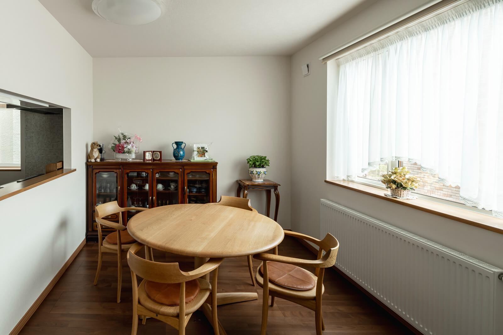 ワイドなFIX窓からの光が心地よいダイニング・キッチン。大きな丸いダイニングテーブルや椅子は新たに購入したもの