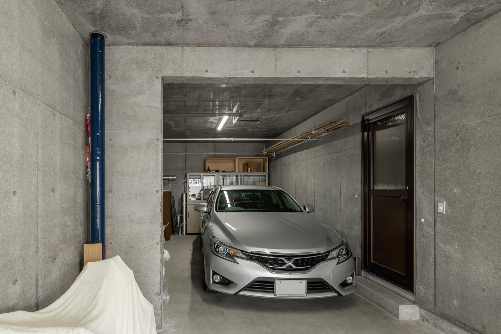 車2台が停められる広いガレージ。「車から屋外に出ることなく家の中に入れるのがとても便利。広さがあるので、棚を置いて収納スペースとしても利用しています