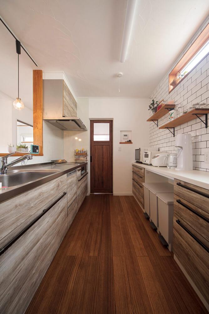 たっぷり収納できるキッチン背面収納は奥さんのお気に入り。奥の扉は玄関ホールへ通じている