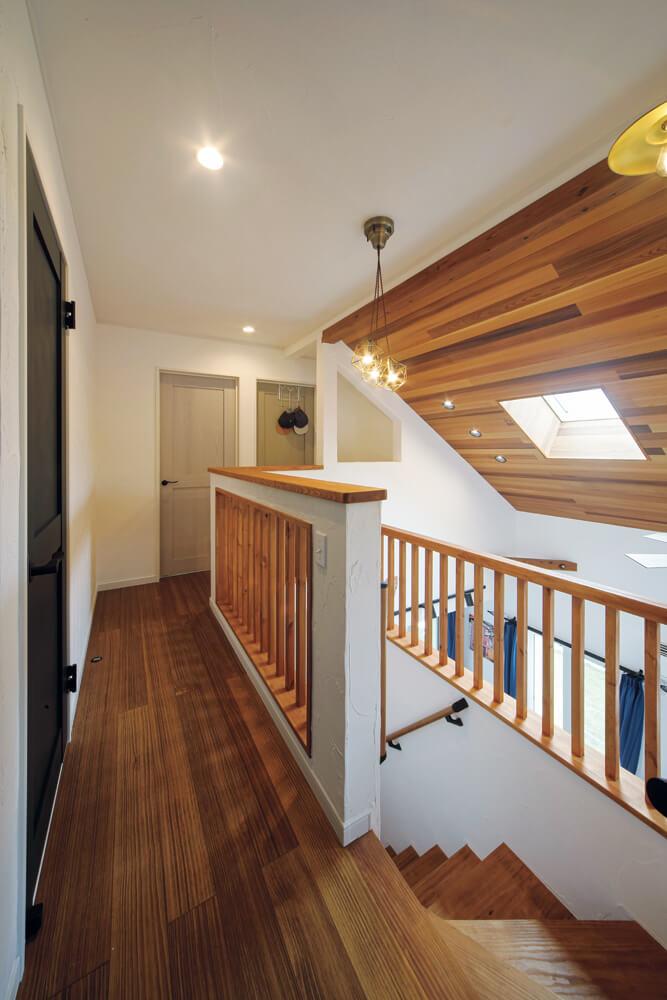 階段まわりは格子にして開放感を演出。浮造り加工の無垢床は足触りが気持ちよく、一年中裸足で過ごしているそう