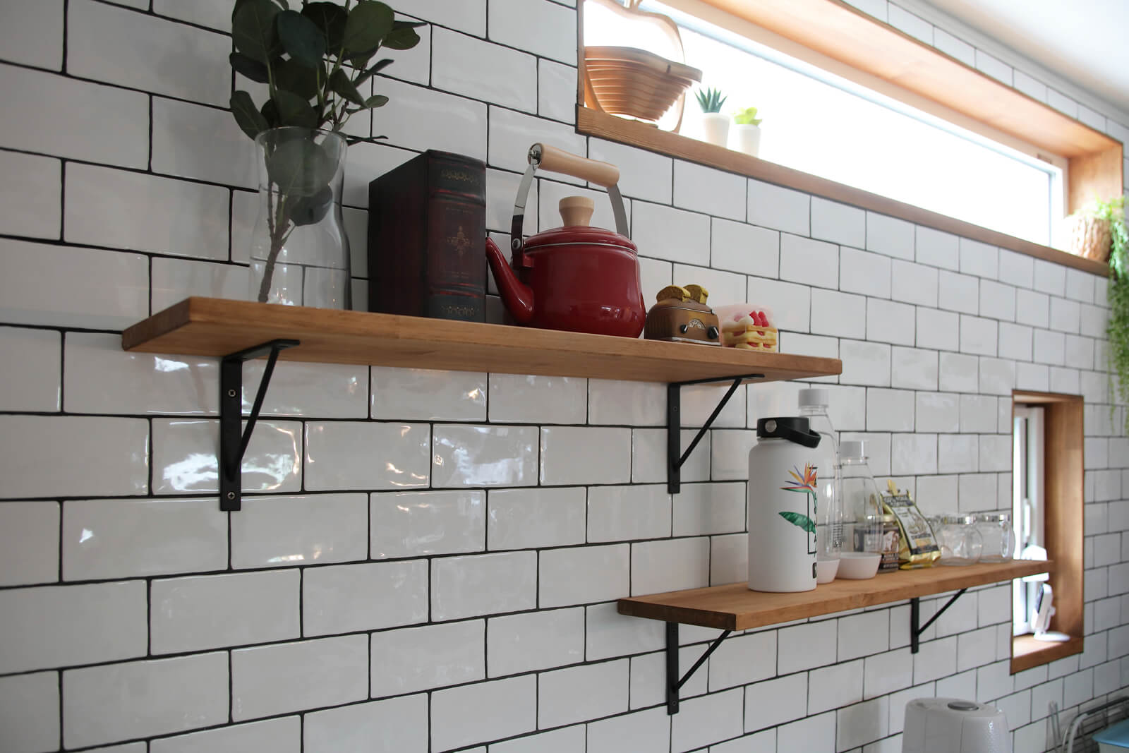 キッチンの壁には真っ白なサブウェイタイルがあしらわれた。見せる収納を希望した奥さんのために、キッチンの背面には飾り棚を造作