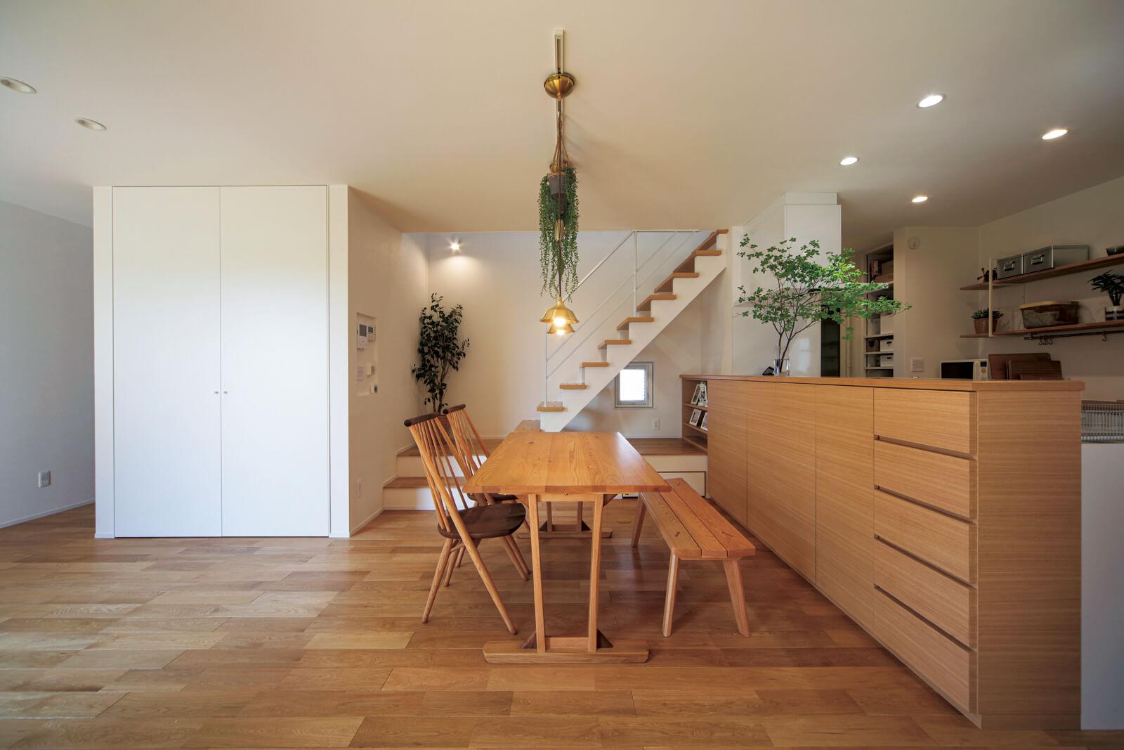 リビングからダイニング・キッチンを望む。対面キッチンの腰壁は全面造りつけ収納になっていてスッキリ。オープンなリビング階段はYさんの希望
