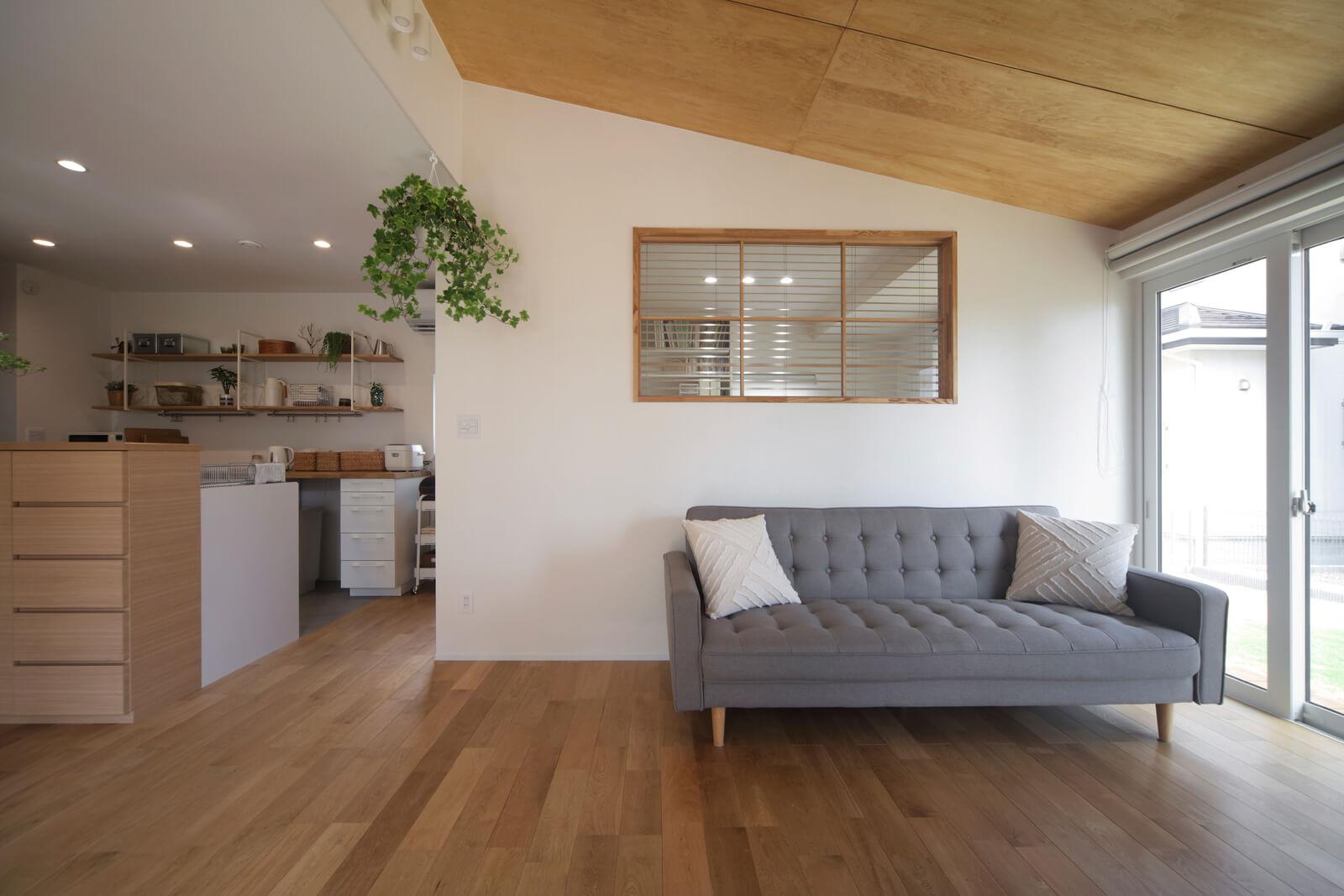 リビングと洋室の間に取り付けた木枠の内窓がおしゃれ。勾配天井はシナベニヤ張りにしてナチュラルな風合いを演出