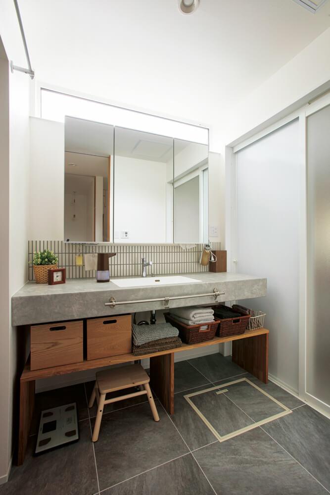 高窓からの光で明るいユーティリティはゆとりのある広さ。水まわりはグレーを効かせてモダンな空間に仕上げている。木製ラックは洗面台幅に合わせて造作したもの